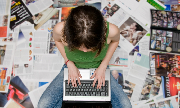 Teen sitting on newspapers with laptop